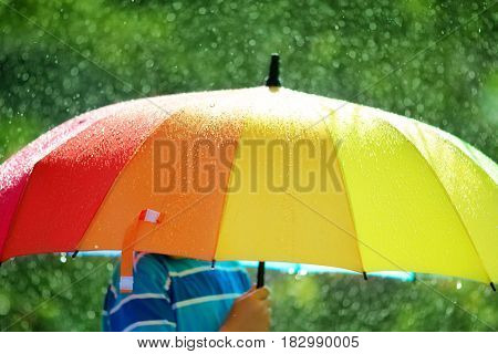 Child on rainy weather. Boy holding colourful umbrella under rain in summer
