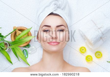 Spa Woman Beauty Treatments. Close-up portrait of beautiful girl with a towel on her head with clean fresh young skin. Applying facial mask. Middle aging woman in spa salon