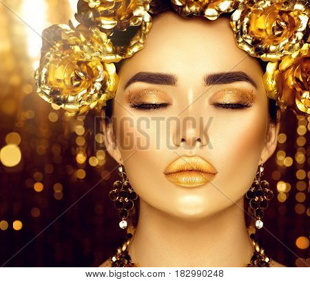 Gold Woman holiday makeup. Beauty fashion model girl with Golden make up, flowers hairstyle and jewellery on glowing background. Gold wreath and necklace. Fashion art portrait