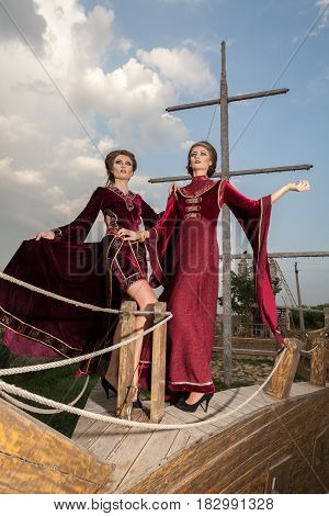 Two ladies in vintage high fashion clothes on a boat. Luxury and glamour