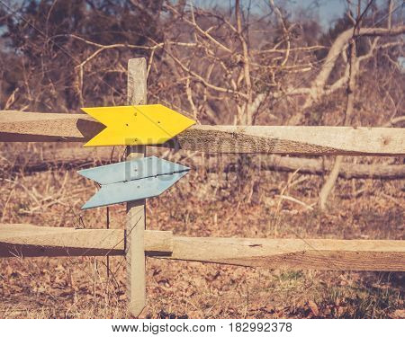 Blank signs in yellow and blue attached to wooden fence post