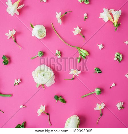 Floral pattern made of white ranunculus, snapdragon, freesia and leaves on pink background. Flat lay, top view. Summer background.