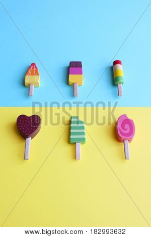 Colorful wooden ice cream over a pastel background.
