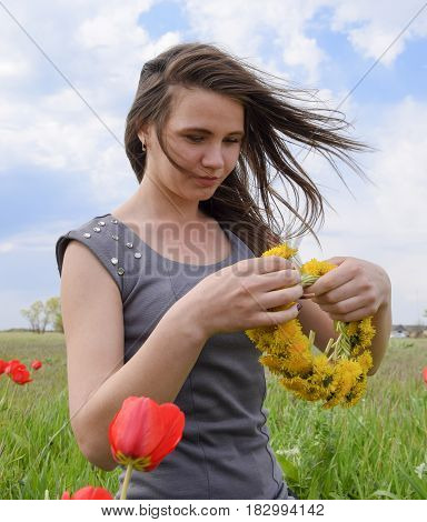 A Girl With A Wreath Of Dandelions In Her Hands. Field Of Tulips