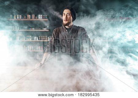 Vape Shop. Man Is Smoking E-cigartte. Cloud Of Vapor.