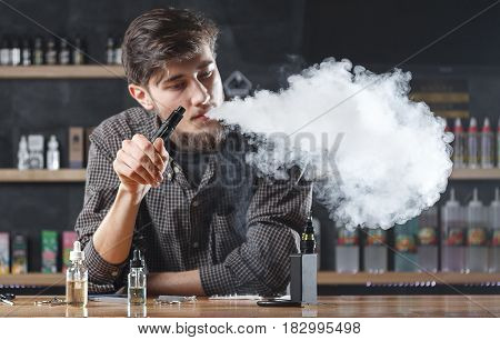 Vape Bar (shop). Vaping Man Is Smoking E-cigarette. A Cloud Of Vapor.