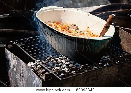 On The Grill Stands A Cauldron In Which To Prepare Meat And Vegetables