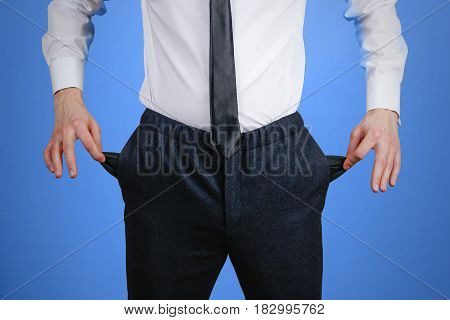 The Businessman In A White Shirt And Black Trousers Shows His Empty Pockets. Isolated On Blue Backgr