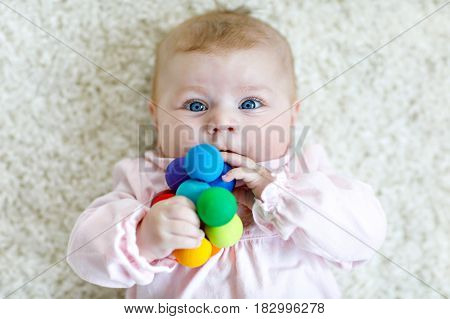 Cute adorable newborn baby playing with colorful wooden rattle toy ball on white background. New born child, little girl looking ath the camera. Family, new life, childhood, beginning concept