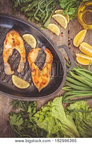 Baked Steak Trout Fish In Cast-iron Form, Around Greens, Leaves, Lettuce, Lemon, Olive Oil, Pepper,