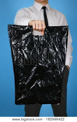 Man Shows Black Blank Plastic Bag Mock Up Isolated. Empty White Polyethylene Package Mockup. Consume