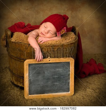 Newborn baby of mixed race sleeping in an antique wooden bucket