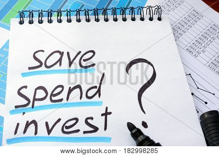 Note with words save spend invest and marker.