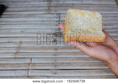 Bread in hand in hand on bamboo background