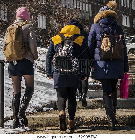Teenagers walk down the street, schoolgirls, climb the stairs, back view