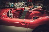 Mechanic working on car body details in restoration workshop poster