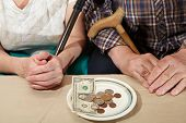 Old couple and small coin. Poverty. Senior people health care poster