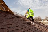 Construction worker putting the asphalt roofing (shingles) with nail gun on a large commercial apartment building development poster