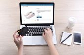 Woman use ecommerce webshop for buy shoes with holding credit card poster