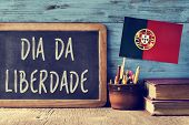 the text Dia da Liberdade, the Day of Freedom national holiday in Portugal written in Portuguese in a chalkboard, and a flag of Portugal, on a rustic wooden table poster