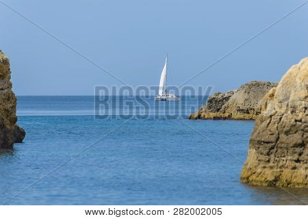 White Sailing Yacht Sailing In The Sea Among The Rocks