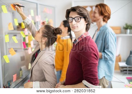 Young Serious Casual Businessman Looking At You While Standing By Noticeboard On Background Of His C