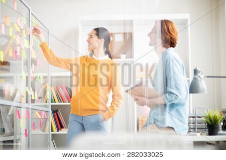 One Of Young Casual Managers Pointing At Notepaper On Noticeboard While Consulting With Colleague At