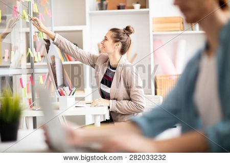 Young Woman Pointing At Working Notes On Noticeboard While Sitting By Desk In Front Of Computer Moni