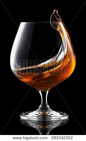 Splash Of Brandy In Snifter Glass Isolated On Black Background