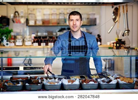 Young Business Owner Standing Behind The Counter Of His Restaurant. Kitchen Behind