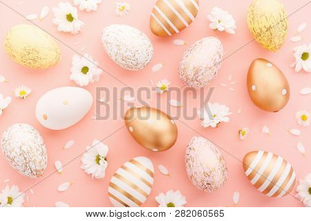 Flat Lay Of Golden Easter Eggs Pattern With Small Flowers And Petals On Pink Background. Easter Back