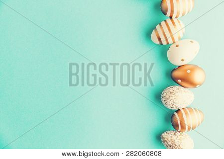 Flat Lay Of Golden Easter Eggs In Row Placed On Turquoise Background. Easter Background Or Easter Co