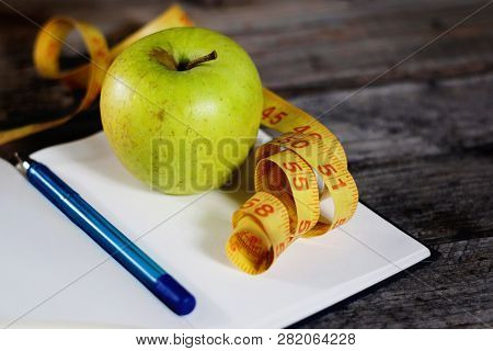 Diet Plan, Empty Notebook, Pencil, Green Apple And Measuring Tape, Flat Lay On Wooden Background.