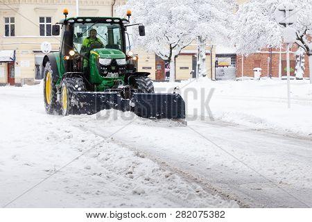 Sodertalje, Sweden - February 3, 2019: Green John Deere Tractor Plowing Snow On The Storgatan Street