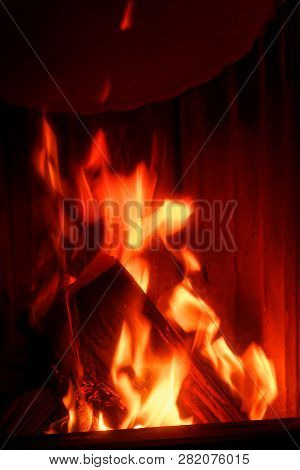 Red Fire Flames In A Stove. The Firewood Is Burning