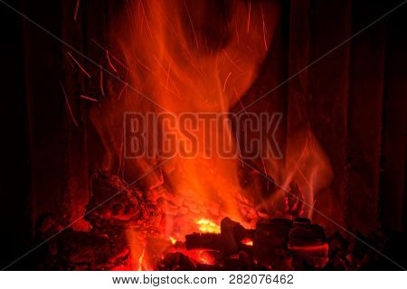 Red Flames From Burning Wood In A Fireplace At Home