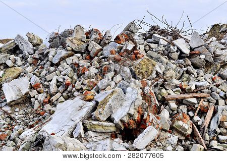 The Rebar Sticking Up From Piles Of Brick Rubble, Stone And Concrete Rubble.