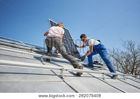 Male Workers Installing Stand-alone Solar Photovoltaic Panel System. Electricians Mounting Blue Sola