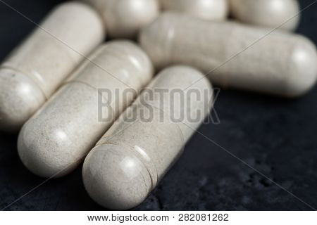 White Medical Capsules Of Glucosamine Chondroitin, Healthy Supplement Pills On A Dark Background, Ma