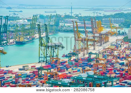 Aerial View Of Singapore Commercial Port, Stacks Of Shipping Conteiners, Freight Cranes And Cargo Sh