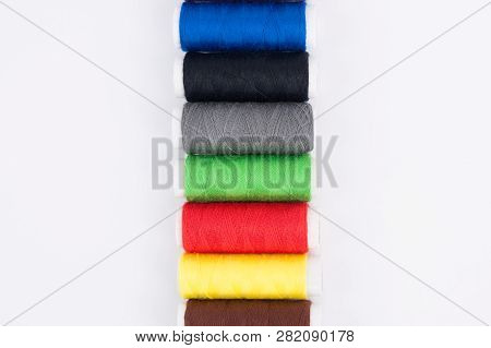 Row of bobbins of new colorful threads on white background. Top view poster