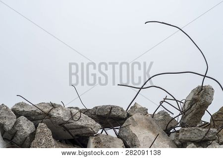 The Rebar Sticking Up From Piles Of Brick Rubble, Stone And Concrete Rubble Against The Sky In A Haz