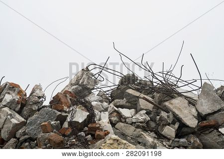 The rebar sticking up from piles of brick rubble, stone and concrete rubble against the sky in a haze. poster