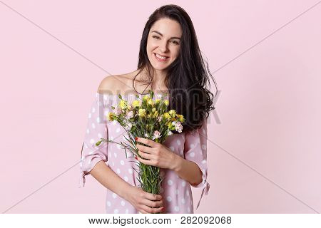 Smiling Brunette Young European Woman Has Toothy Smile, Holds Bouquet Of Pretty Flowers, Wears Dress