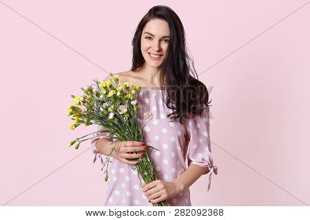 Waist Up Shot Of Good Looking Smiling Brunette Woman Expresses Happiness, Recieves Flowers From Boyf