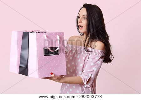 Studio Shot Of Surprised Brunette Young Lady Has Bated Breath, Holds Many Bags, Returns From Shop Wi
