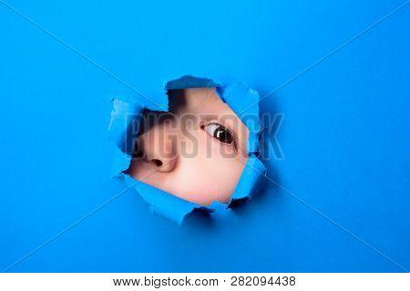 Through Paper. Kid Looking Through Paper. Spy Eye Watching Through A Hole. Child's Eye Looking Throu