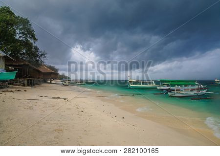 Sandy Beach With Moored Indonesian Boats On The Tropical Island Of Gili Meno. Heavy Leaden Clouds Hu