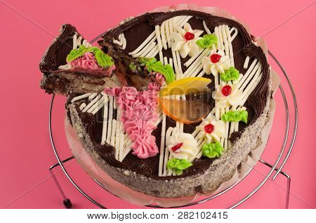 Dissected Tasty Round Chocolate Cake And One Piece Of Cake On Shiny Metal Grid On Pink Background