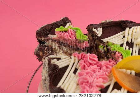 Dissected Tasty Round Chocolate Cake And One Piece Of Cake On Pink Background